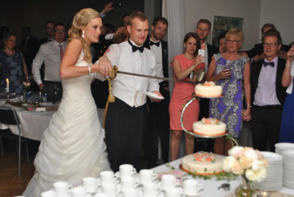 Bröllopstårta skuren med svärd