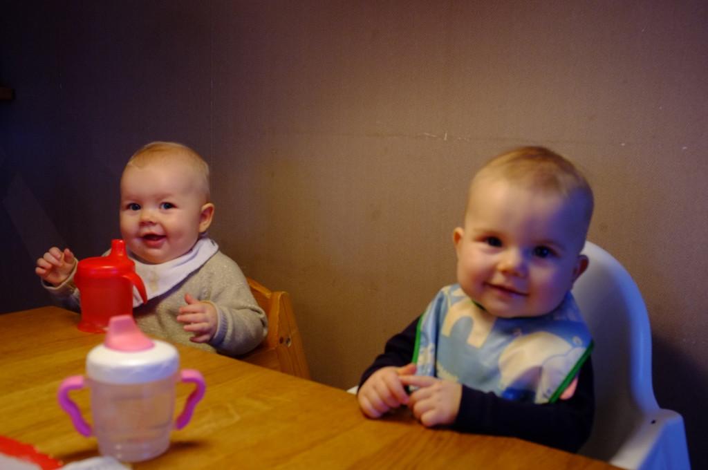 Linnea och Clara vid köksbordet, glada